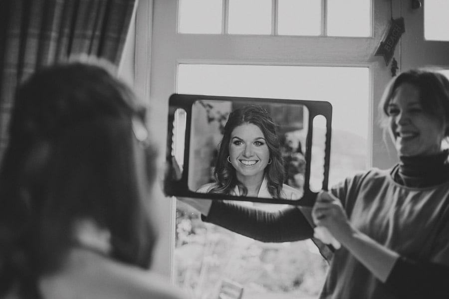 The make up artist holds a mirror up and shows the bride a reflection of her face