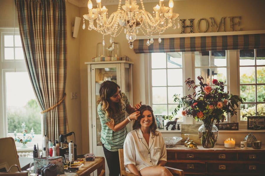 The hair stylist stands above the bride and attends to the brides hair in the back room