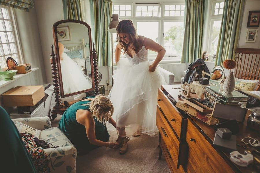 A bridesmaid puts on the brides shoes as the bride lifts her dress up