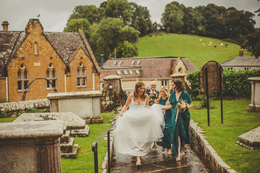 The bride walks up towards the front of the church as a bridesmaid walks next to her holding her wedding dress to stop it getting wet