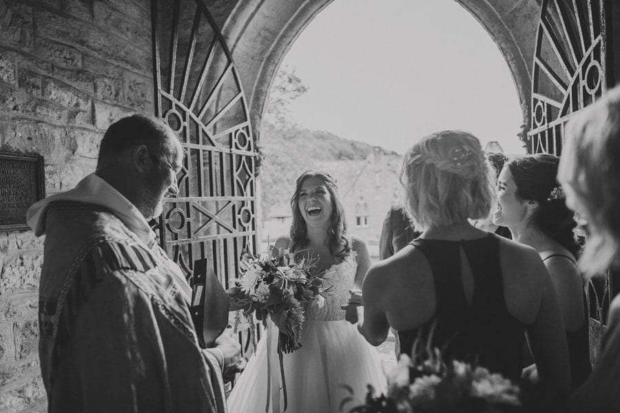 The bride laughs with her bridesmaids and Father as she listens to the vicar outside the church
