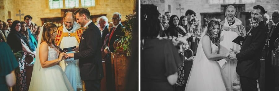 The bride places a ring on the finger of the groom inside the church and the vicar watches on