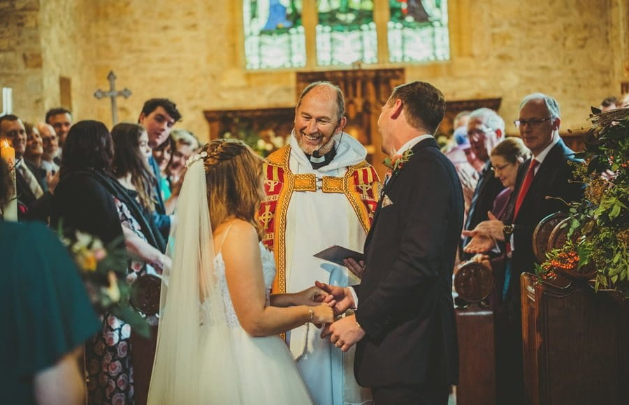 The vicar smiles at the bride and both the bride and groom laugh at the vicar in the church