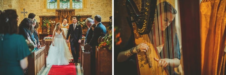 The bride and groom walk back from the alter hand in hand and a lady plays a harp