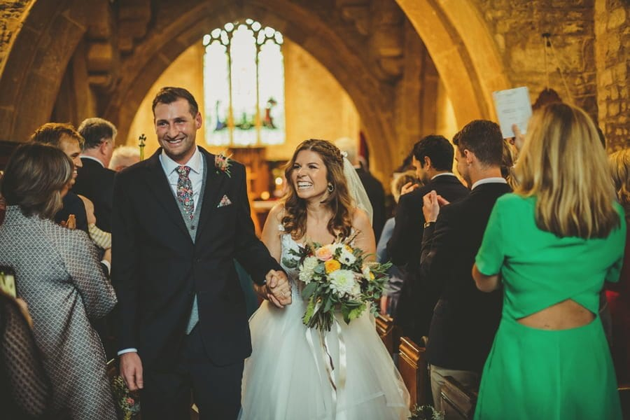 The bride and groom smile at wedding guests as they walk towards the door of the church