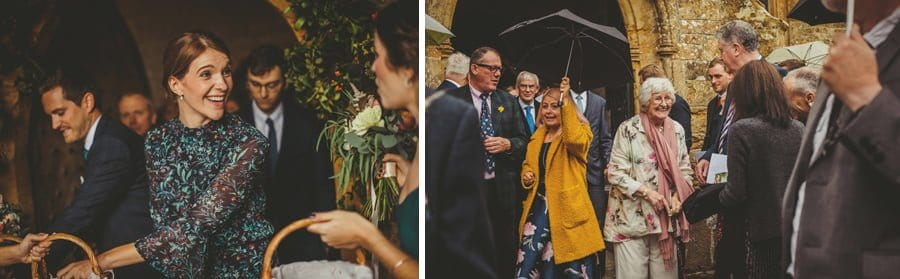Wedding guests walk out of the church and pick up confetti