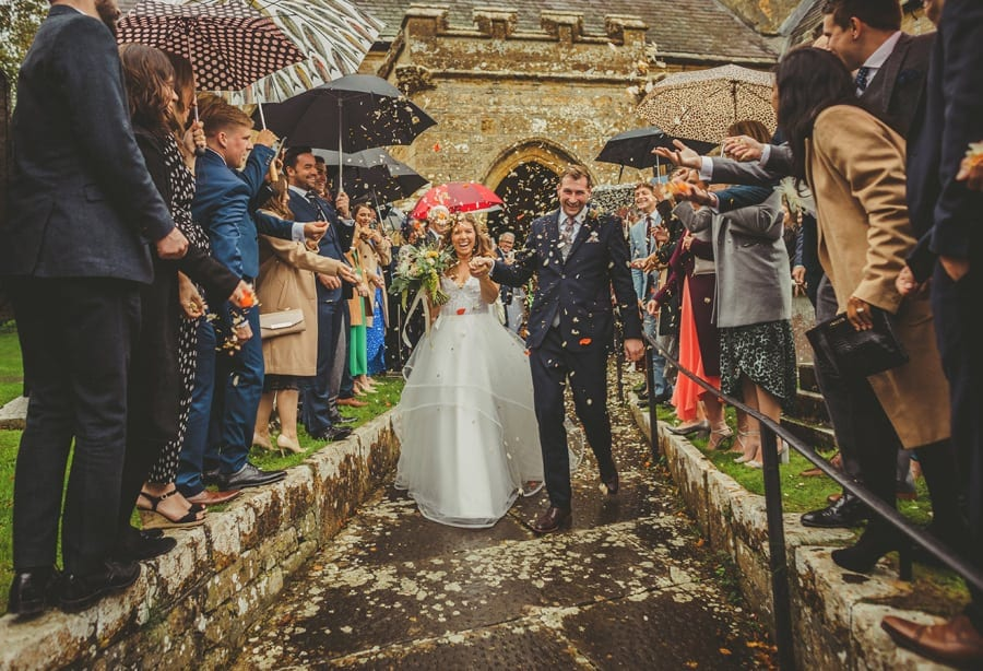 The bride and groom walk down the path of the church as wedding guests throw confetti in the air