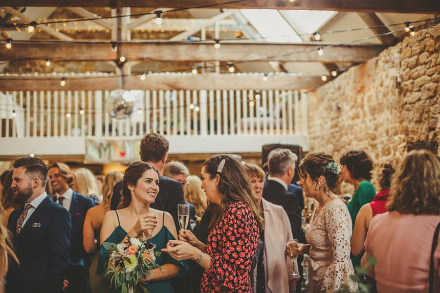 Wedding guests chat one another and sip champagne in The Tithe Barn in Symondsbury