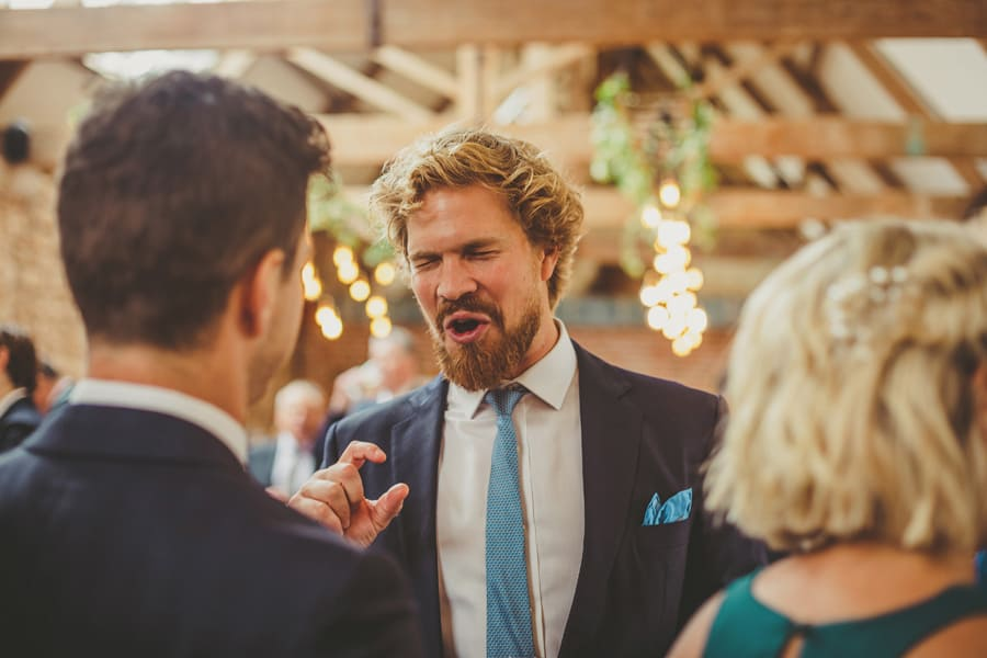 A wedding guest closes his eyes and holds his thumb and finger together as he chats to a man and lady