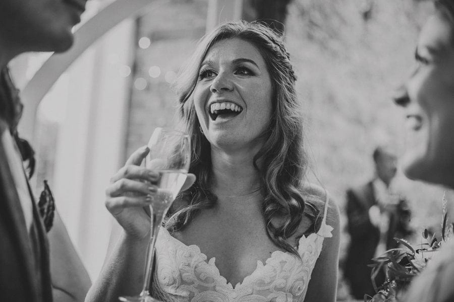 The bride laughs as she talks with her wedding guests