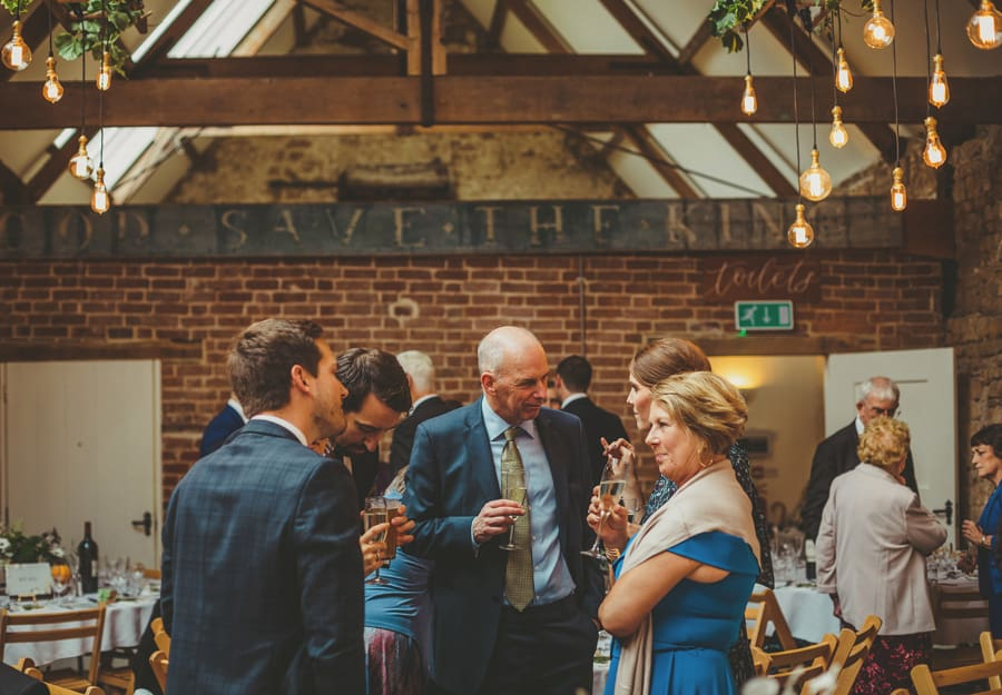 Wedding guests talk amongst themselves in the Tithe Barn