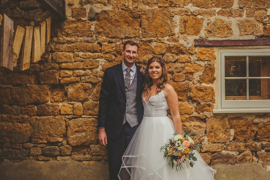 The bride and groom pose for a photograph outside the Tithe Barn in Dorset
