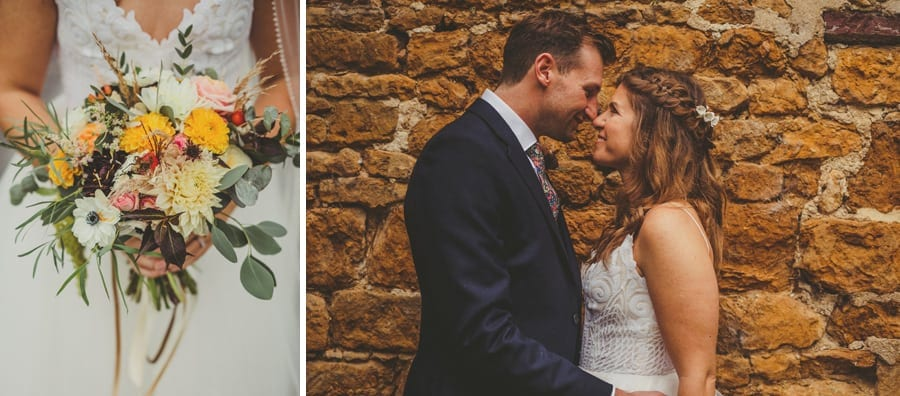 The groom touches his wife's nose, smiles and places his arms around her waist outside the Tithe Barn in Symondsbury