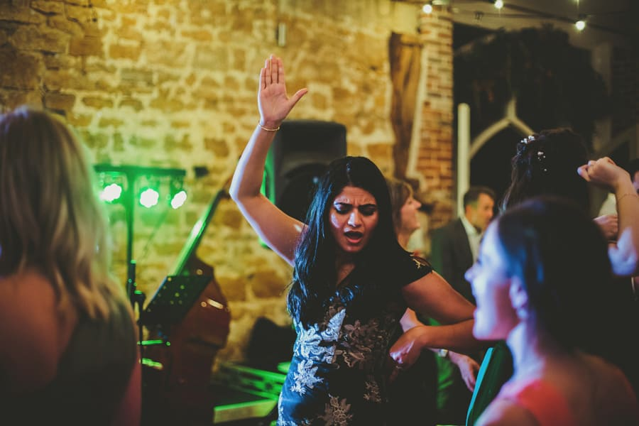 A wedding guest raises her arm in the air on the dance floor