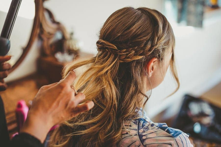 The hairdresser attends to a bridesmaids hair