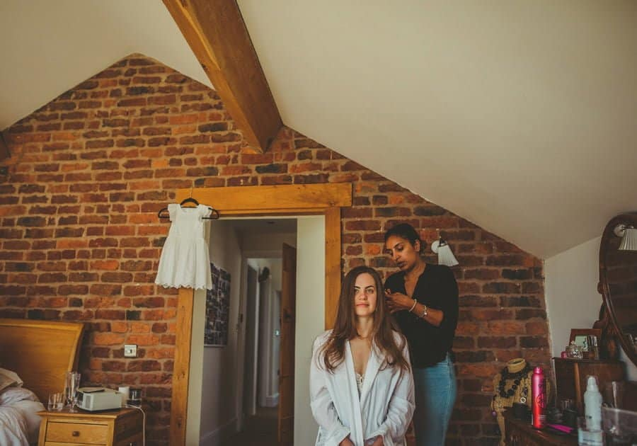 The hairdresser attends to the back of the brides hair