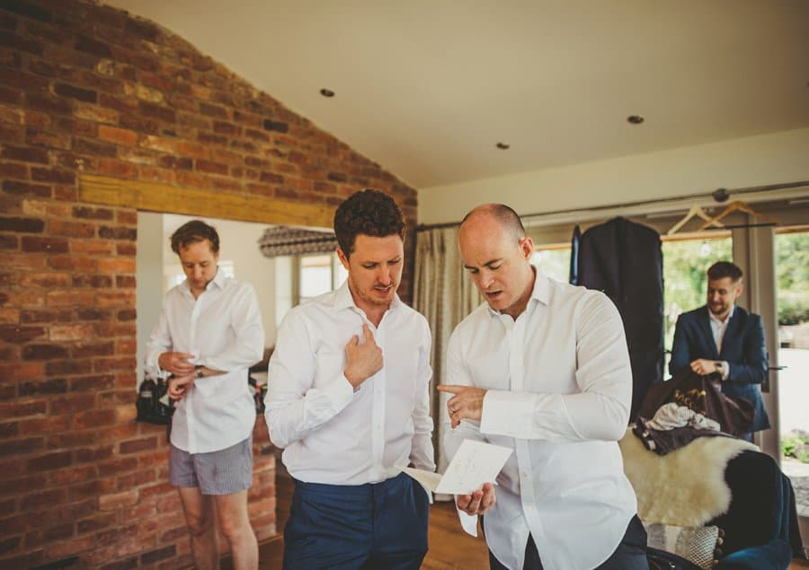 An usher points to the groom and delivers instructions for the outdoor ceremony