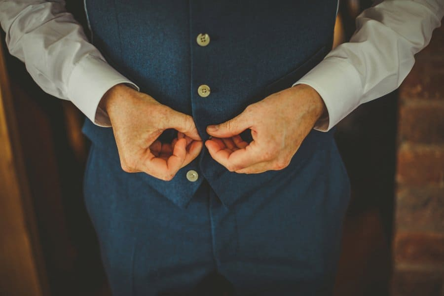 The groom buttons up his waistcoat