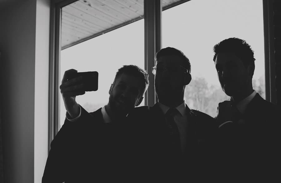 Ushers take a photograph next to the window in their apartment