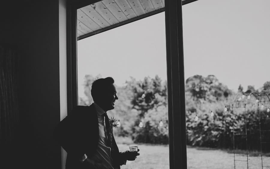 An usher holds a glass of whisky and looks out of the window in his apartment