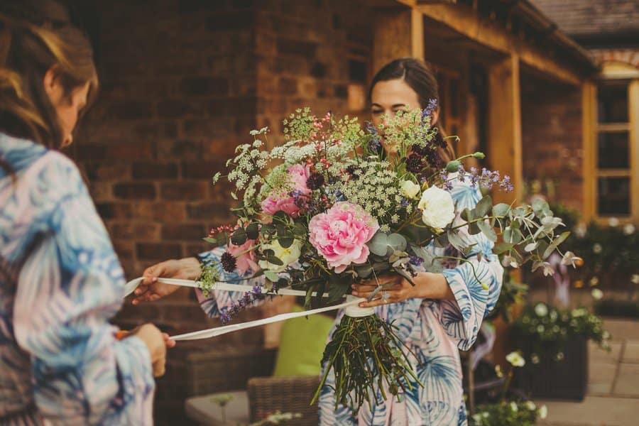 Bridesmaids tying ribbons around the wedding flowers
