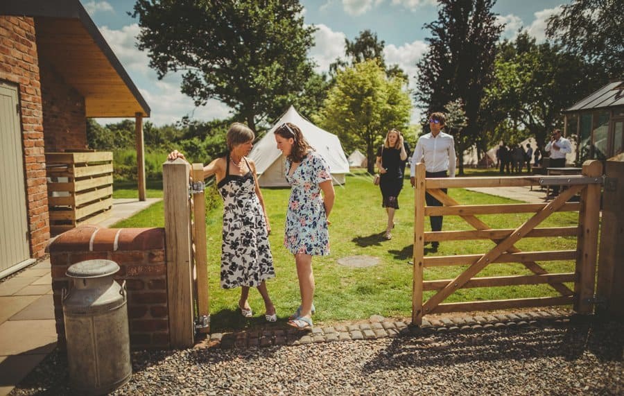 Wedding guests stand next to a large wooden gate in the courtyard at Mill farm