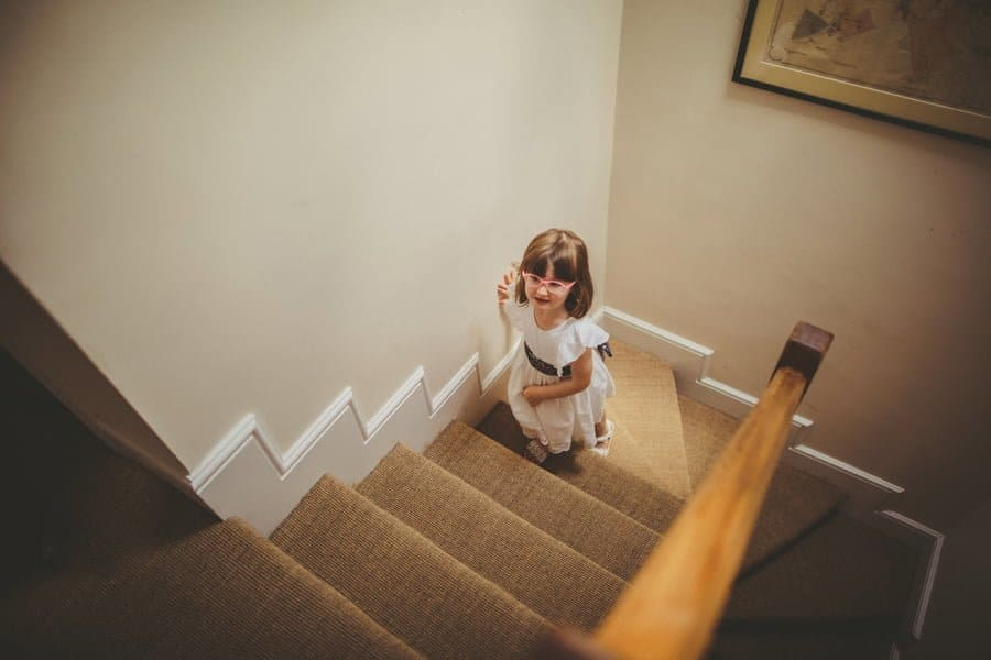 A flowergirl walks up the stairs to watch the bride getting ready