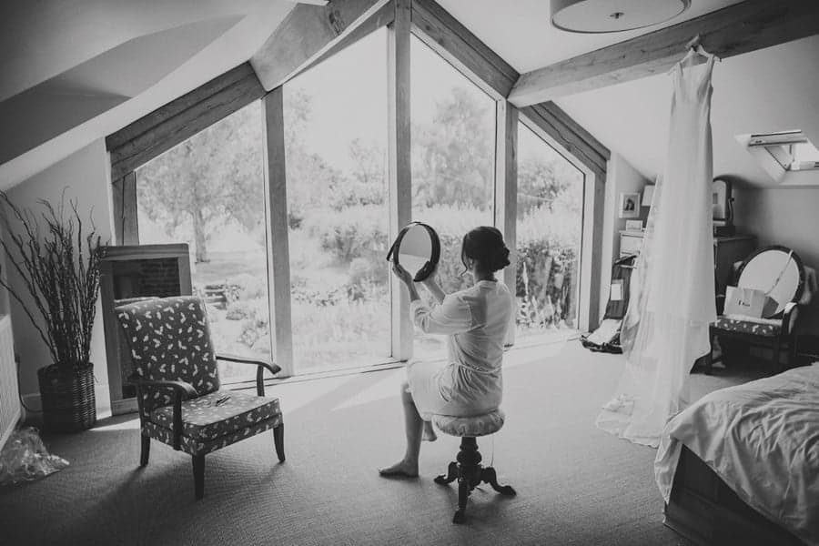 The bride holds up a mirror and looks at herself sat on a stool in the bedroom at Mill farm
