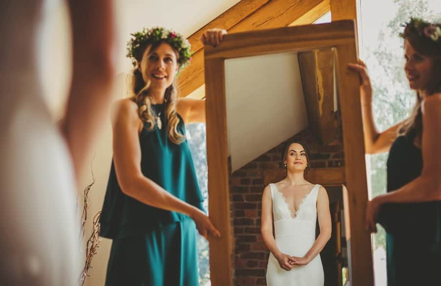 The bridesmaids hold up a large mirror as the bride looks at herself in her dress