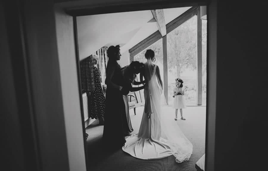Bridesmaids fasten the back of the brides dress as the flowergirl stands and watches on