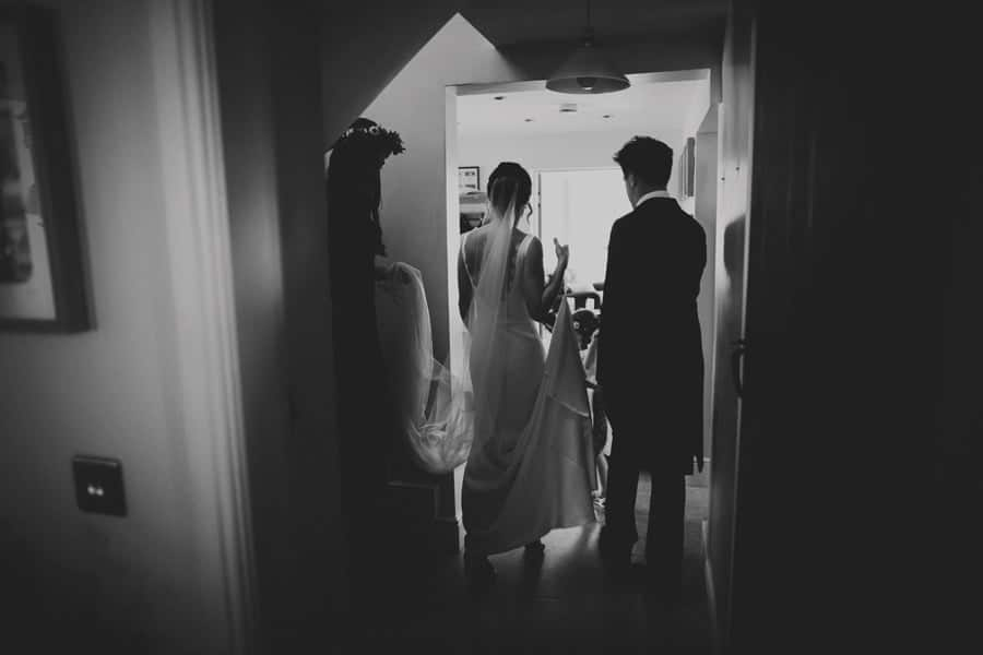 The bride and her brother walking through the house at Mill farm