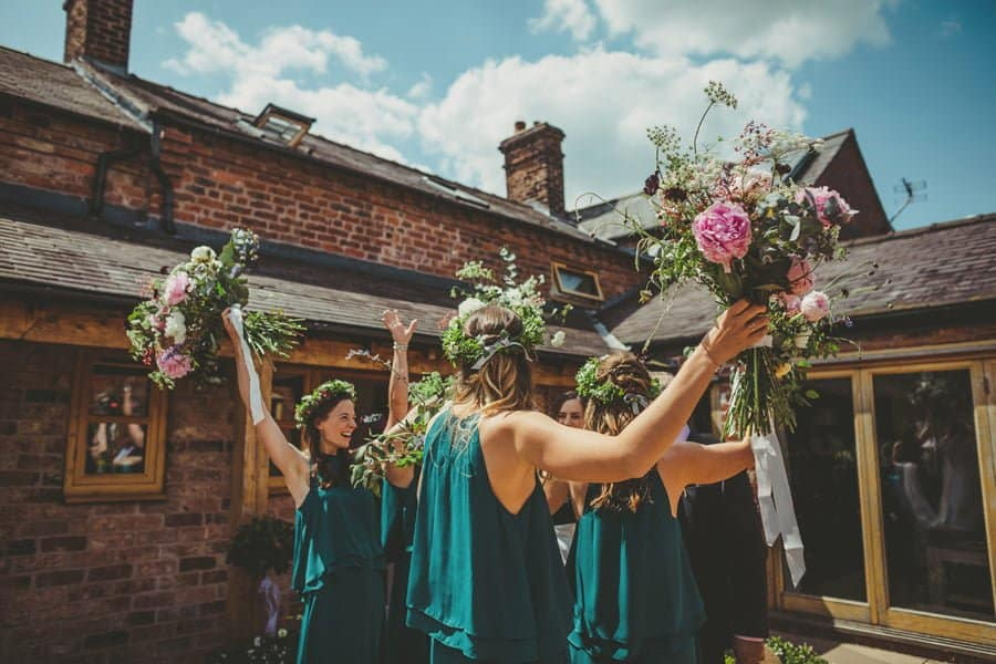 The bridesmaids lift their flowers into the air in the courtyard to celebrate the start of the wedding