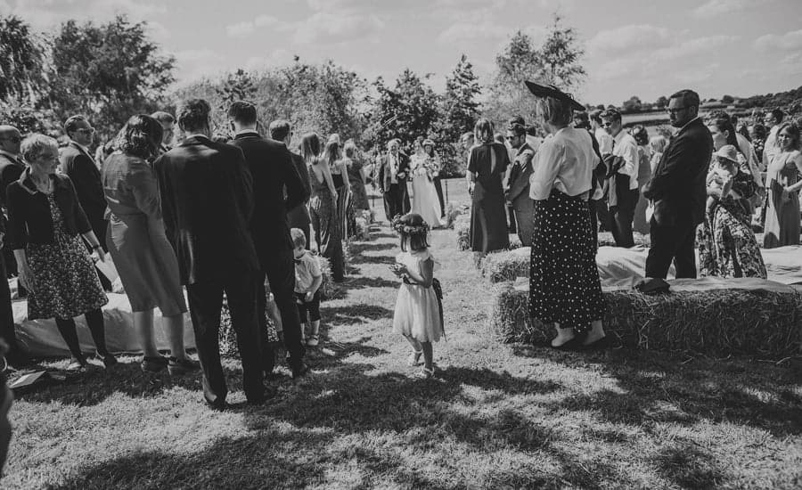 A flowergirl walking down the aisle at the outdoor ceremony