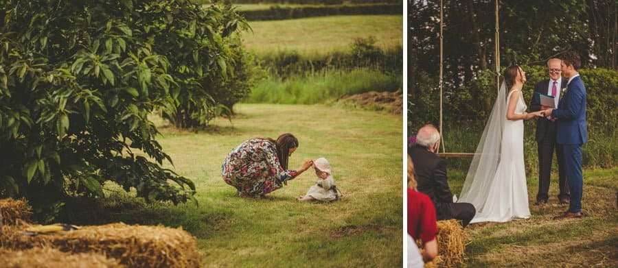 A mother attends to her baby's hat sat on the grass
