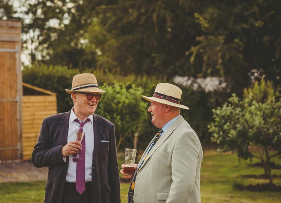 Wedding guests laugh and joke on the lawn