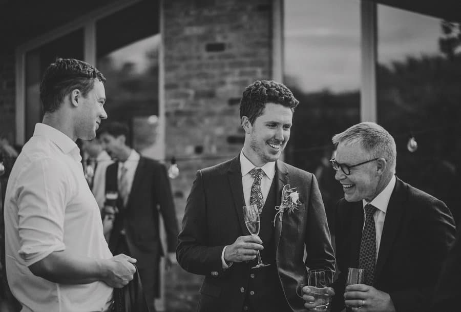 The groom tells a joke to one of his wedding guests