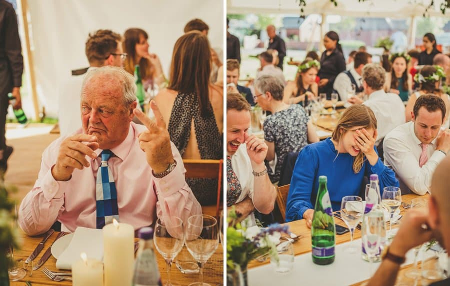 The brides father holds up two fingers and a wedding guests puts her hands to her face and laughs