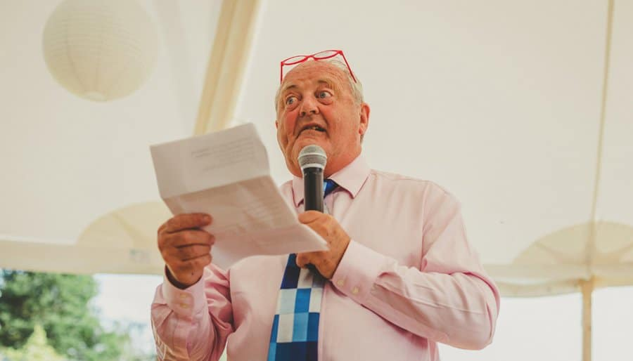 The brides father speaks into a microphone