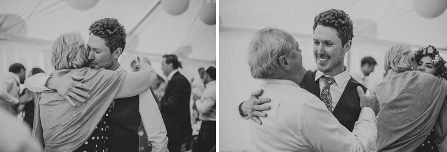 The groom hugs the brides mother and the brides father in the marquee