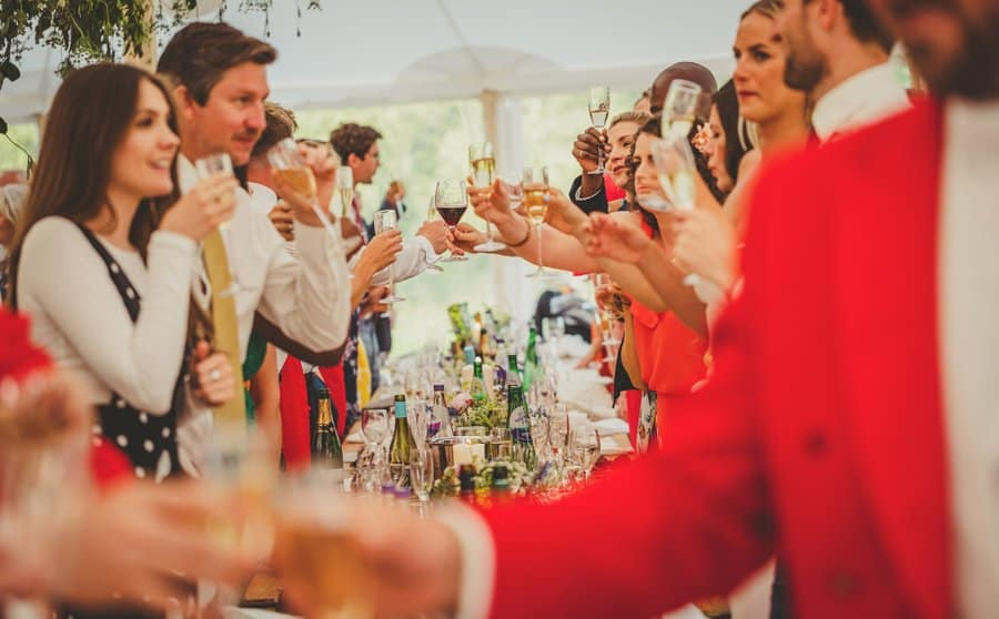The wedding party celebrate by putting their champagne glasses across the table