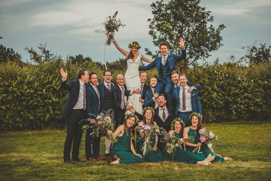 The bride and groom with their ushers and bridesmaids pose for a photograph on the lawn at Mill farm