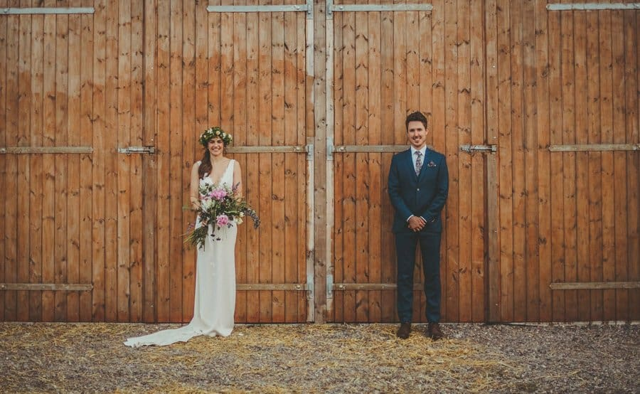 The bride and groom pose for a photograph stood next to the barn doors
