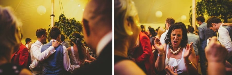 A friend of the groom places his arm over the grooms shoulder and a lady claps her hands on the dancefloor