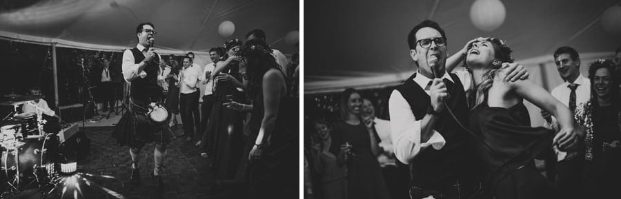 An usher sings a song through a microphone and dances with a bridesmaid in the marquee