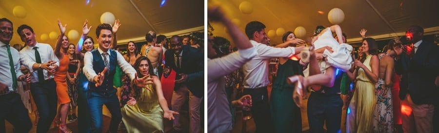 The groom holds his hands out and catches the bride as she runs into him