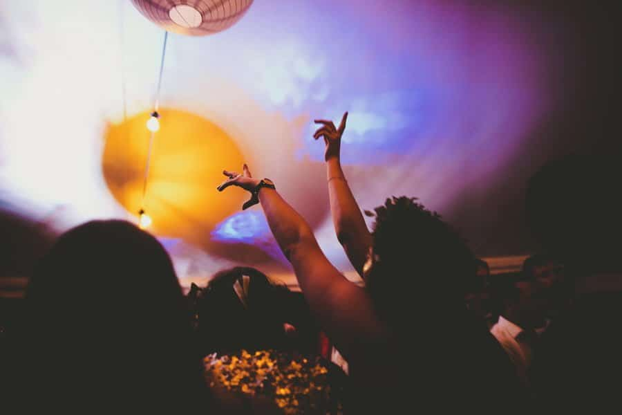A wedding guest raises her arms into the air and dances in the middle of the marquee