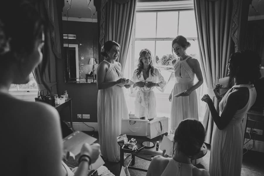 The bride and her bridesmaids laugh and joke with each other