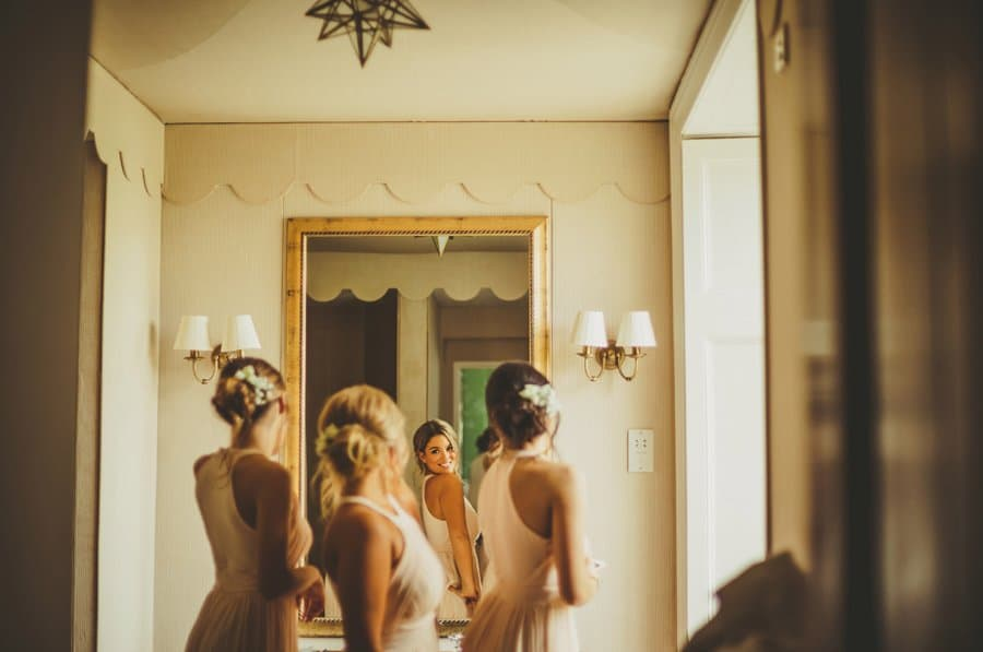 Bridesmaids looking at themselves in the mirror of the bathroom at Stubton Hall