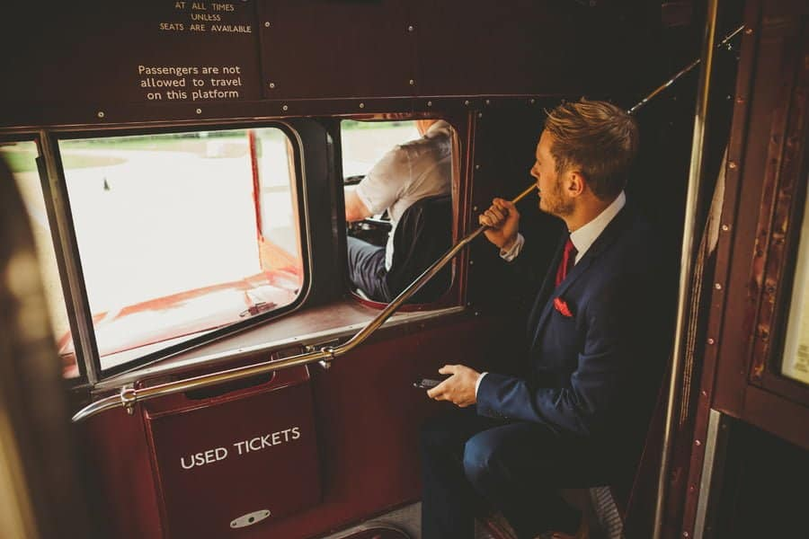 A wedding guest sits on the stairs of the wedding bus holding his mobile phone