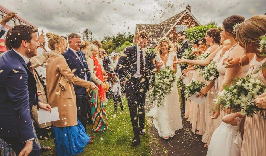 The wedding guests throw confetti over the bride and groom outside the church
